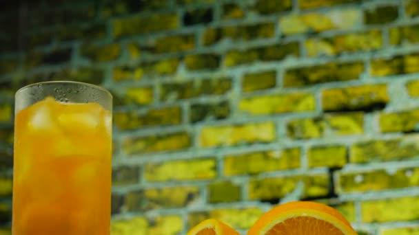 Gelbe Limonade mit Eis in einem transparenten Glas. Orangensaft in einem Glas auf dem Hintergrund einer gelben Ziegelwand