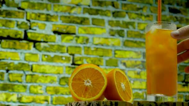 Cocktail an der Bar. Ein Mann rührt einen kalten Cocktail mit Eis an. Gelbe Limonade in einem transparenten Glas. Orangensaft