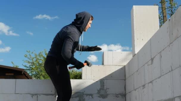 Muž na staveništi. Muž si staví dům vlastníma rukama, mladý muž během zdiva zarovnává kostky bílých cihel. Rovná cihla s kladivem