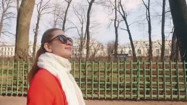 Mladá blonďatá žena chůze v Evropské Park a úsměvy na slunný jarní den