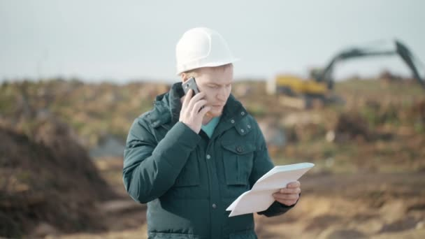 Engineer Speak on Phone, Looking Documents and Calls Worker on Background of Excavator