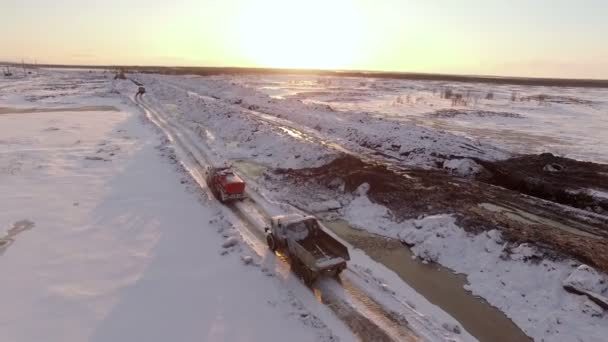 aerial sunset view of vehicles convoy driving on snow-covered winter road