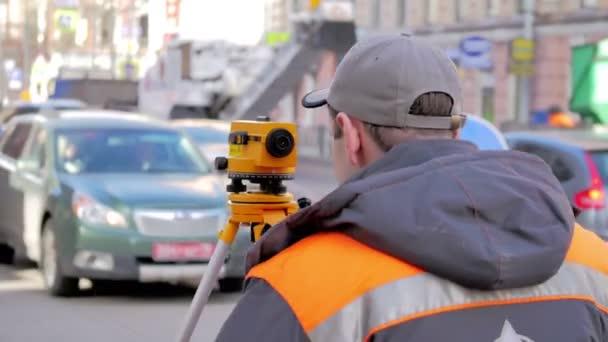 Inženýři používají tacheometer nebo teodolit pro průzkum linie v centru města, na pozadí práce na silnici