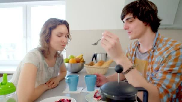 Coppia bere tè e guardando ogni altri occhi. Uomo che alimenta il suo girldriend con il cucchiaio di gustosa torta