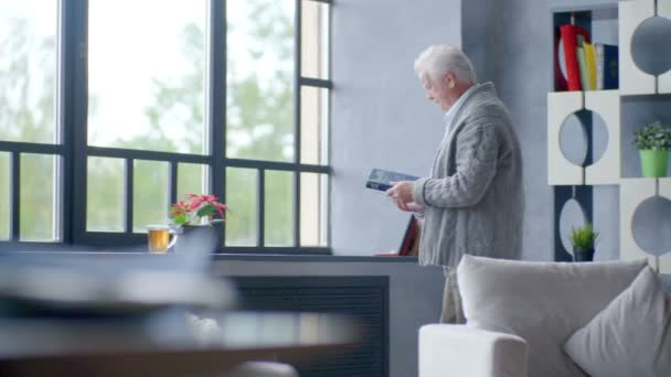 elderly caucasian man reading a book and drinking a delicious tea in a modern apartment