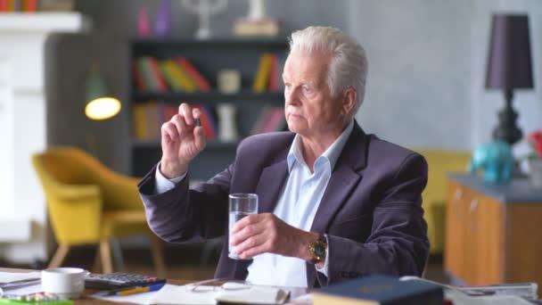 Boldogtalan szomorú és zavaros idős ember ránéz egy pirulát, és vigye