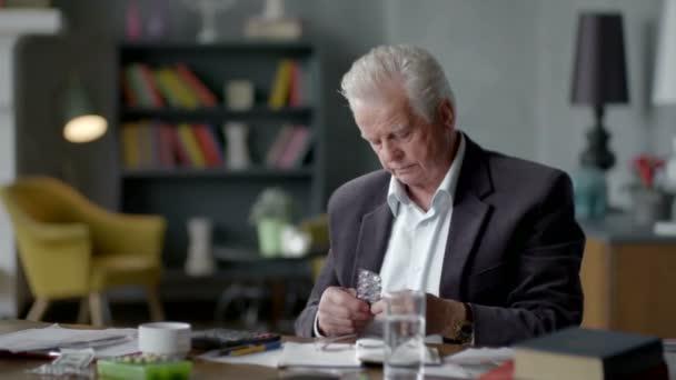 Boldogtalan, idős ember szomorú és zavaros hitetlenkedve nézi egy tabletta