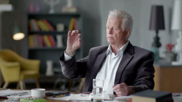 Boldogtalan szomorú és zavaros idős ember hitetlenkedve nézi egy pirulát, és vigye