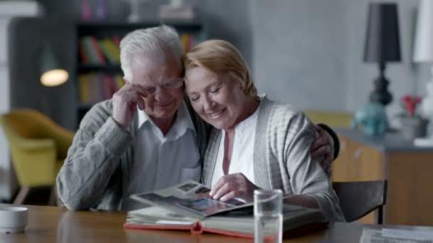 Coppie felici anziane trascorrere del tempo insieme e nostalgico. sono alla ricerca di vecchi album di foto e sorridente