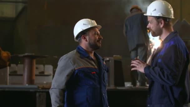 zwei Ingenieure besprechen wichtige Etappen des Aufbaus in Schwerindustrie Fabrik. Schweißer-Hintergrund