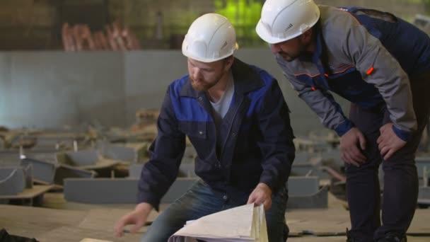 Inženýři se na stavební plány a diskutovat etap výstavby v těžkém průmyslu továrně