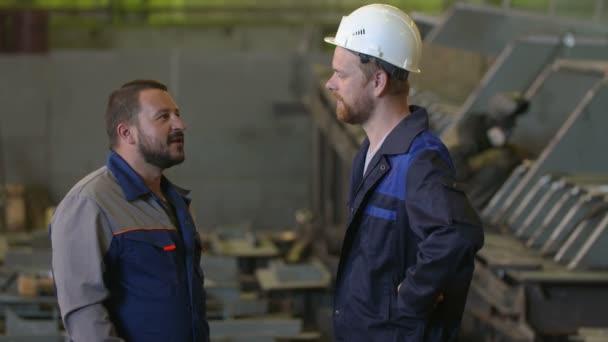 dva technici diskutovat etap výstavby v továrně těžkého průmyslu. svářeč pozadí