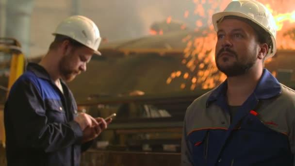 portrét dvou vážných inženýrů v práci v továrně těžkého průmyslu. Sparks a svařování pozadí