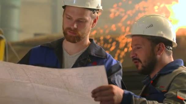 portrét dvou vážných inženýrů prozkoumat projekt v továrně těžkého průmyslu. svařování pozadí
