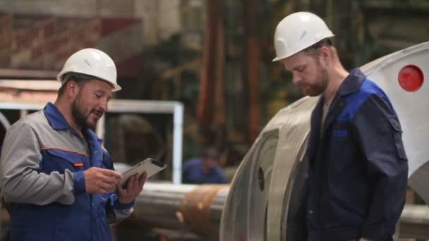 dva technici s přenosným počítačem komunikovat a úsměv v těžkém průmyslu továrně