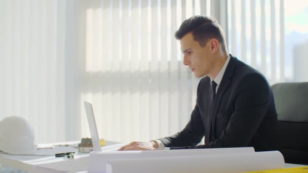 Sebevědomý a úspěšný mladý podnikatel. Pohledný muž v obleku, práce s počítačem v moderní kanceláři
