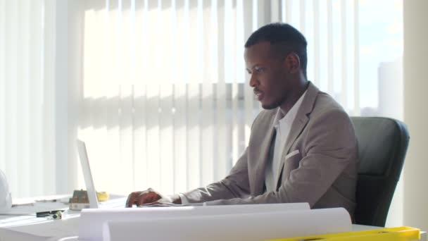 Schwarze jungen Geschäftsmann mit Laptop-Computer in einem modernen weißen Büro sitzen