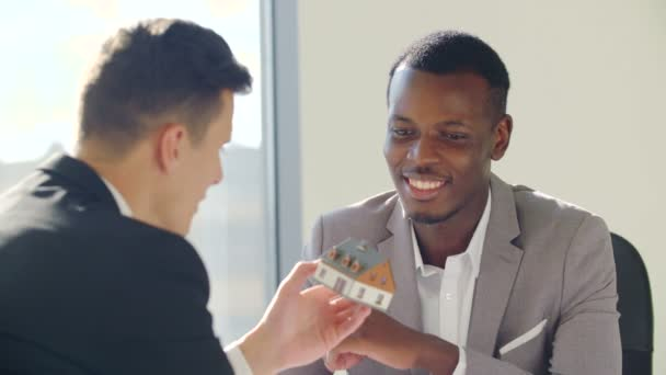 Real-estate black agent with man signing contract in white office
