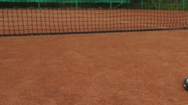 Tenisová raketa a nový tenisový míček na čerstvě natřeném tenisovém kurtu