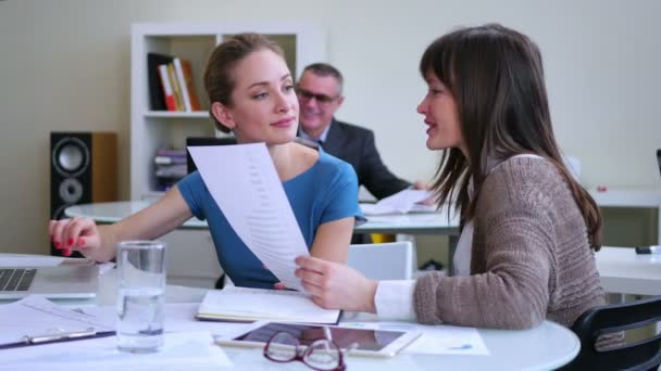 Two beautiful businesswomen are working in a light and modern office