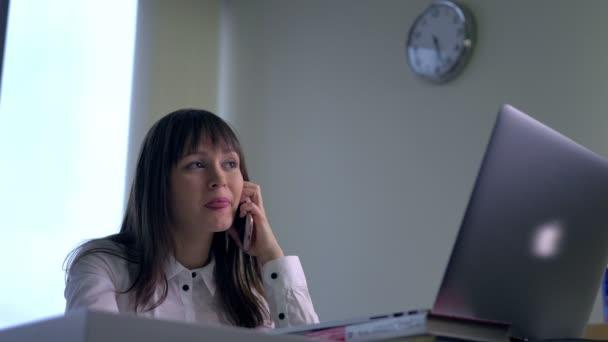Podnikatelka hovoří v telefonu a pracovat na stolním počítači