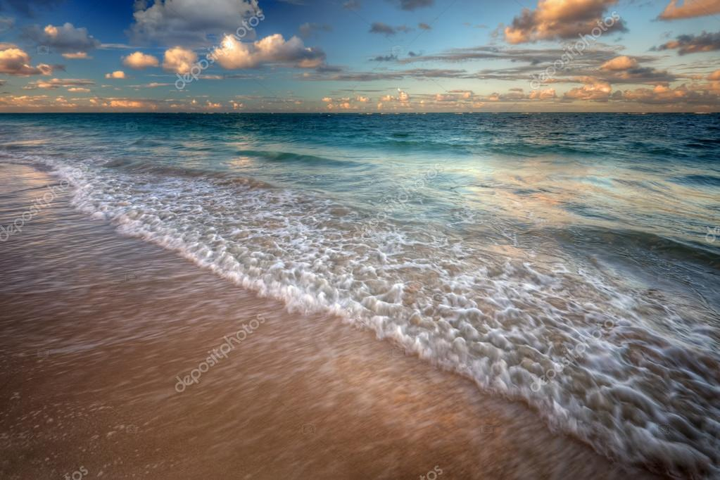 Waves cresting onto a sandy beach