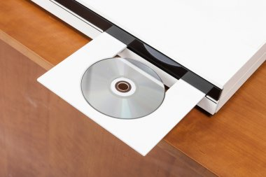the wood desk(table) with white CD player, empty(blank) CD(blue ray, DVD) isolated white.