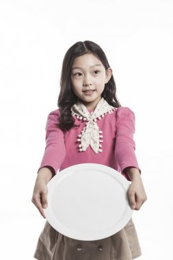 A girl(kid) holding a white dish