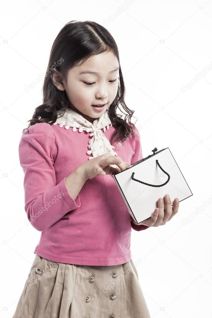 A kid wearing pink blouse, white scarf with paper bag.