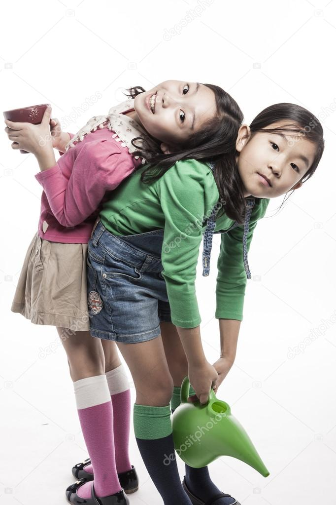 Two kids(girl) with watering tool, pot