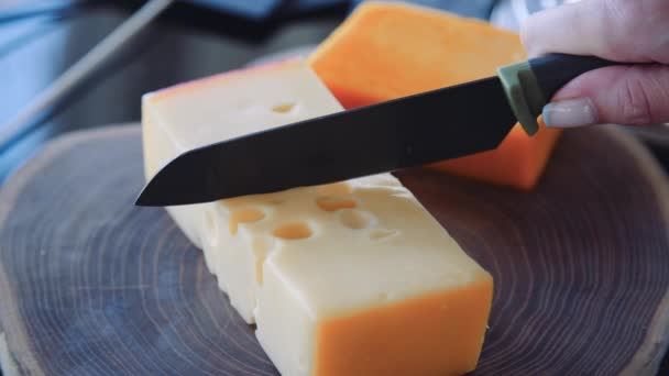 kuchařka krájí sýr nožem na dřevěné desce