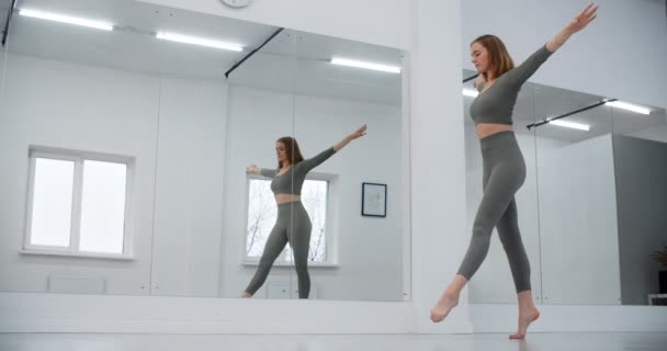 Gymnast jumps infront of mirror wall at the white hall in slow motion, gymnastics in the white hall, yoga and pilates trainer, 4k 120p Prores HQ