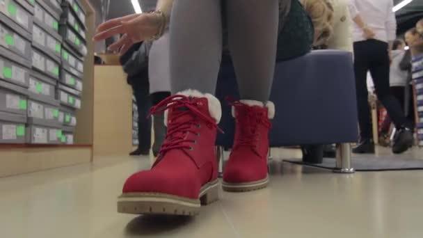 Žena se snaží na červené zimní boty v obchodě s obuví