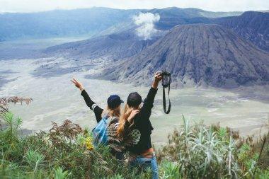 women standing looking  at volcano