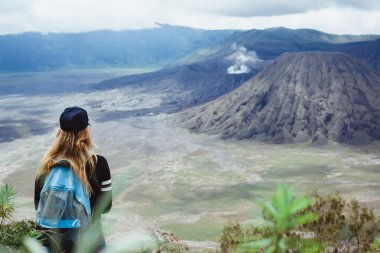 girl standing looking  at volcano