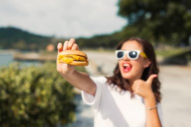 girl in glasses eating fast food