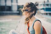 Fényképek lány ül a tengeri pier napszemüveg