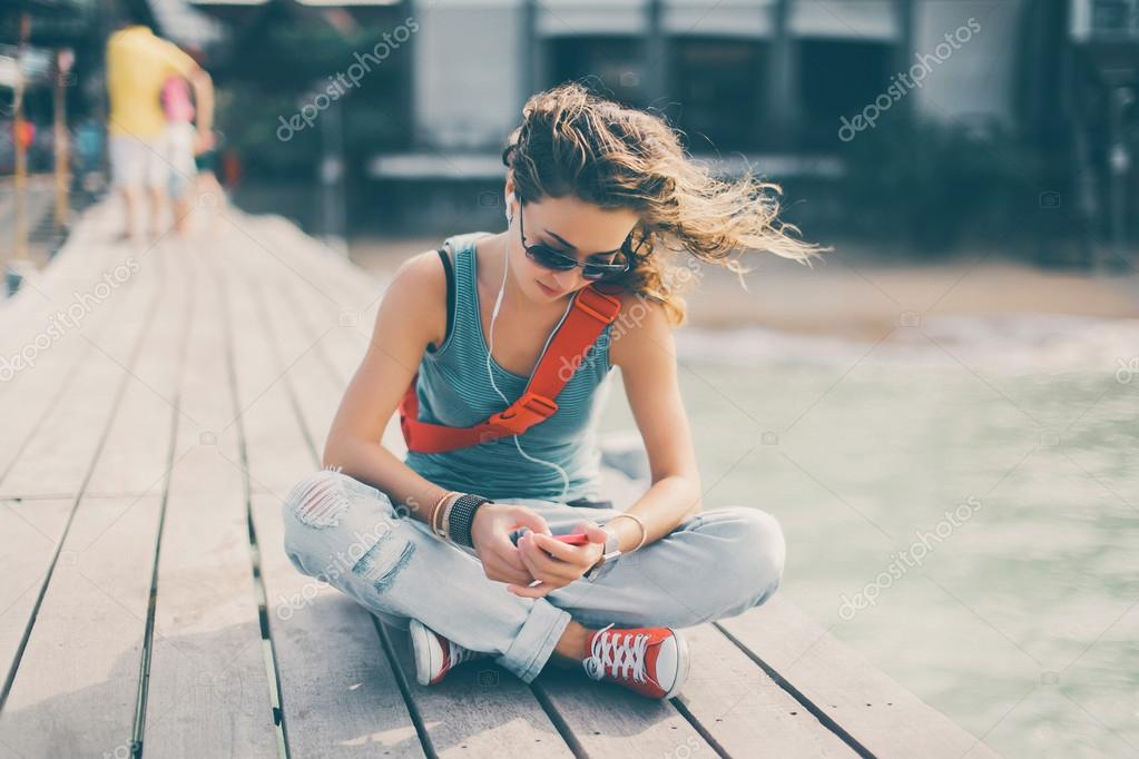 girl in sunglasses sitting on the sea pier