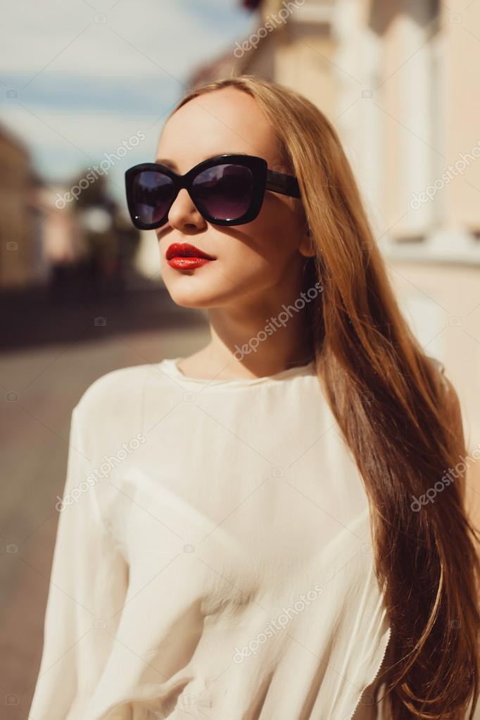 724a29a17 Beautiful blonde girl in sunglasses posing with red lips on the street the  wind in your hair sun street fashion clothing — Photo by sergey_causelove