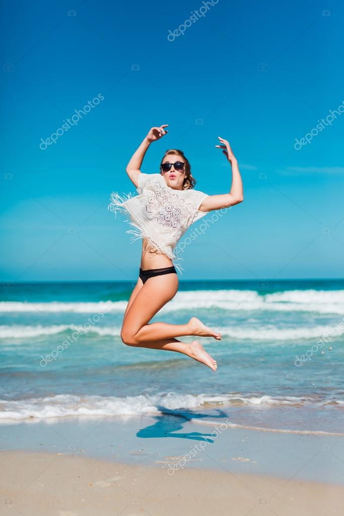 girl in glasses jumping on the beach