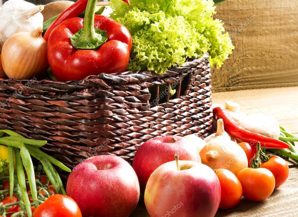 плетеная корзина с фруктами и овощами на деревянный стол