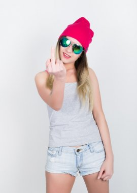 teenager girl in denim shorts and a gray T-shirt and a pink knit hat, tied at the hips plaid shirt. showing middle finger. girl in sunglasses