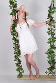 Fényképek full-length Beautiful young leggy blonde in a little white dress and white cowboy hat on a swing, wooden swing suspended from a rope hemp, rope wrapped vine and ivy