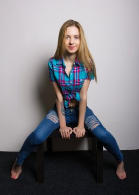 sexy young girl in jeans and a plaid shirt posing sitting on the coffee table