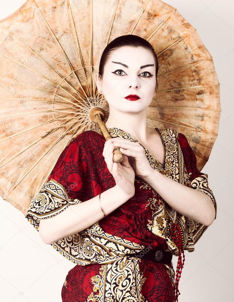 05840f7ee Hermosa chica vestida como una chica geisha sosteniendo un paraguas ...