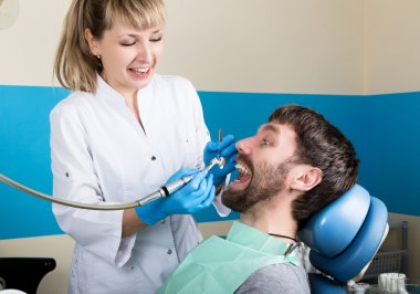 The reception was at the female dentist. Doctor examines the oral cavity on tooth decay. Caries protection. doctor puts the patient an anesthetic injection.