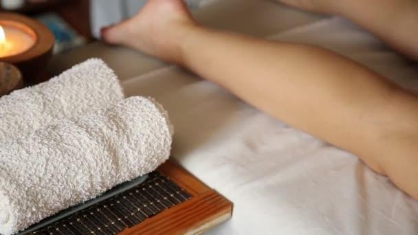 mladá žena dostane masáž chodidel v wellness salonu. detail svíček