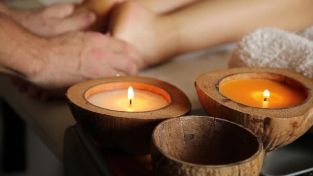 young woman gets a foot massage in the spa salon. close-up of candles