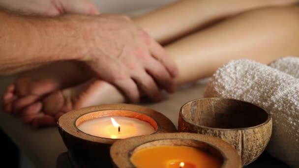 junge Frau bekommt eine Fußmassage in der Spa-Salon. Nahaufnahme der Kerzen. männliche Hände gleiten an den weiblichen Beinen