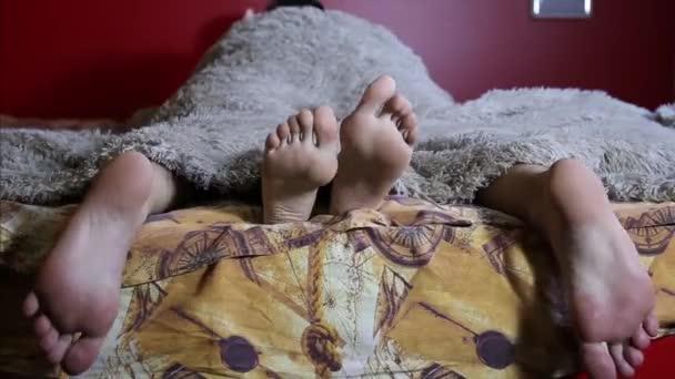 Zwei Paare von männlichen und weiblichen Füße unter die Decke zu sehen. schlafen Sie zusammen, beim Sex Liebhaber. paar im Handumdrehen Intima